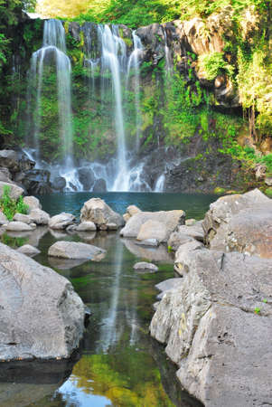 Low shot of majestic waterfall with huge rocks in the foreground Stock Photo
