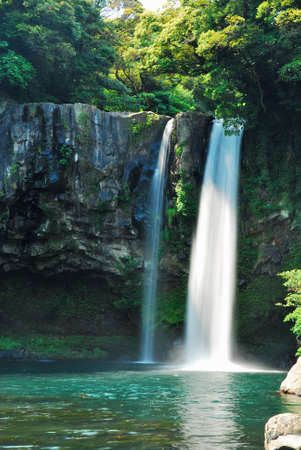 Low shot of majestic waterfall falling into blue pond