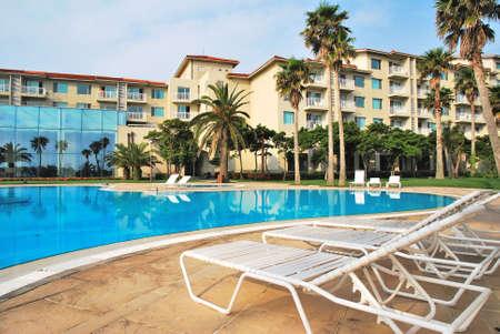 hospedaje: Sillas de playa a un lado de la piscina tropical con �rboles de coco reflexiones resorts de lujo en el fondo