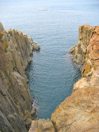 treacherous: Looking down into the sea from a treacherous looking cliff