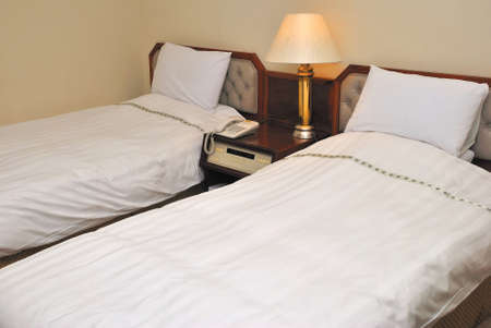 Twin beds with table lamps lighted up in a high class hotel room Stock Photo - 5433736