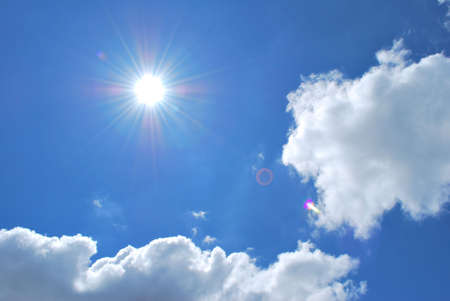 Dazzling sun with blue sky and white clouds background, depicting happiness, hope and joy. photo