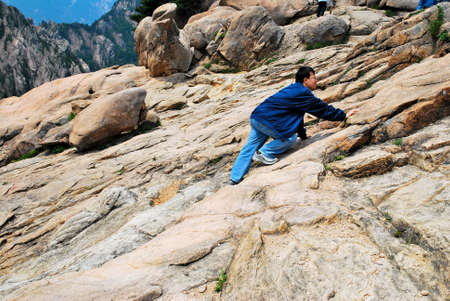 endure: Young man climbing treacherous steep mountain cliff full of rocks and boulders. Suitable for concepts such as determination, strength, power, danger and success Stock Photo