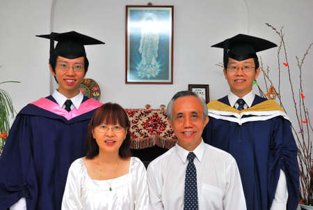 Happy and blissful Chinese family with both sons recently graduated from university.  photo