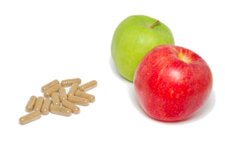 substitution: A red and green apple and a pile of medical capsules. Suitable for concepts such as natural foods and medicine, fruits as substitutes for medicine, healthy eating, healthy lifestyle, dieting and weight loss.