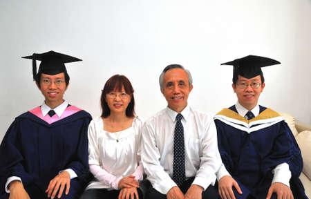 graduacion de universidad: Feliz y dichosa familia china con dos hijos de posgrado. Simboliza la satisfacci�n de vida y logros. Tambi�n es adecuado para conceptos tales como el �xito, el orgullo, la felicidad, el amor y la vida. Foto de archivo