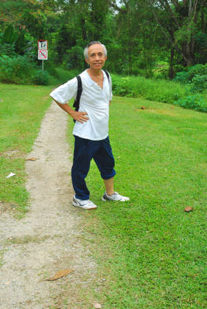 Old Asian hiker at start of hiking or mountain trail. Symbolizes concepts such as health and fitness, travel and relaxation, sports and trekking, and a healthy lifestyle. Stock Photo - 5592337