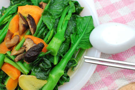 sumptuous: Sumptuous, home cooked Chinese vegetarian cuisine. Ingredients include green, leafy vegetables, mushrooms, carrots, and slices of ginger. Suitable for food and beverage, travel, healthy lifestyle, and diet and nutrition. Stock Photo