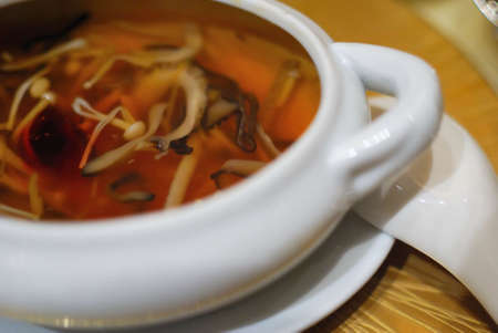 Sumptuous and healthy-looking Asian style vegetarian cuisine. Delicious sharks fin soup cooked with various vegetables, pumpkin, mushrooms, corn and mock meat. Stock Photo