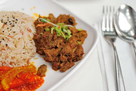 unpolished: Vegetarian rendang chicken or mutton with unpolished red rice. Suitable for concepts such as diet and nutrition, healthy lifestyle, and food and beverage. Stock Photo