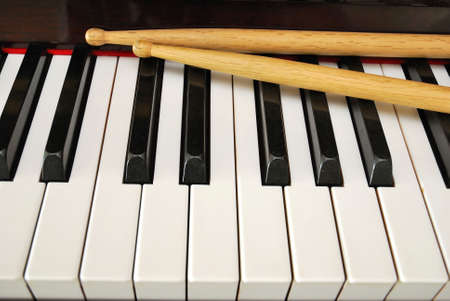 Drum sticks on black and white piano keyboard. For concepts like music and creativity. photo