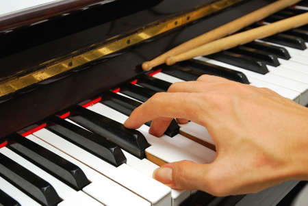 Right hand playing on black and white piano keyboard with drum sticks. For concepts like music and creativity. Stock Photo - 6883853