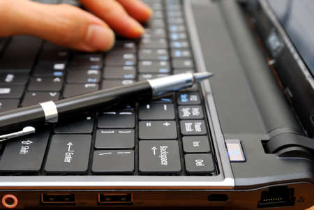 Hand typing on laptop keyboard with pen. For concepts such as electronics and technology, office and business, and work related objects.
