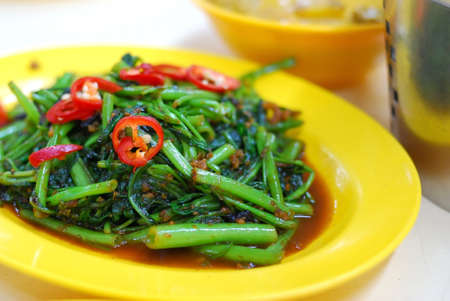 Asian kangkong vegetables cooked with spicy sambal chili sauce. Also known as Ipomoea Aquatica or water spinach. Suitable for food and beverage, healthy lifestyle, and diet and nutrition. Stock Photo