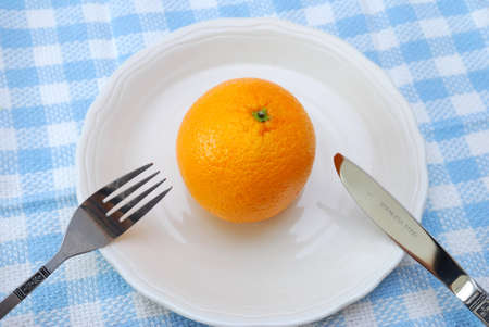 Fork and knife ready to eat orange on plate. Healthy eating and lifestyle, diet and nutrition, and fresh fruit concepts . photo