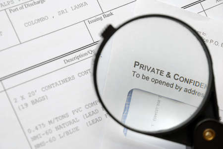 Closeup of magnifying glass on security related text on letter with sensitive business documents in background. For privacy and confidentiality, security and protection concepts. photo