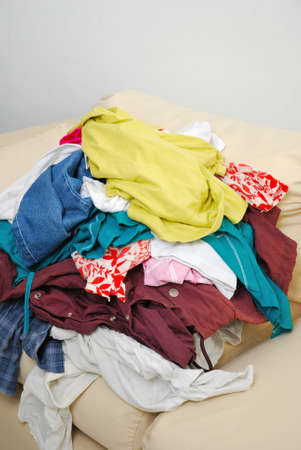 Messy and unfolded clothes on sofa isolated on white background. For lifestyle concepts. Stock Photo