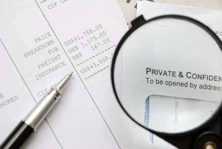 confidentiality: Closeup of magnifying glass on security related text on letter with pen on money related documents in background. For privacy and confidentiality, security and protection concepts.