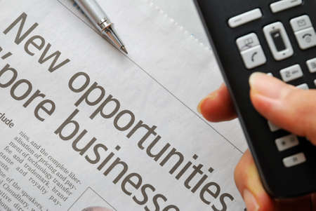 Closeup of new opportunities text on newspaper with hand dialing phone in foreground, signifying business and success, office life and job searching concepts. photo