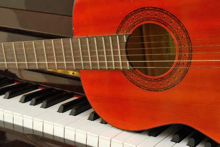 drums: Guitarra ac�stica en el teclado del piano. Para conceptos como la composici�n de la m�sica y la creatividad.  Foto de archivo