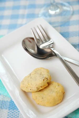 Healthy cookies on white plate with utensils. Filled with nutritious nuts for a healthy afternoon snack or high tea. Concepts such as food and beverage, diet and nutrition, and healthy lifestyle. photo