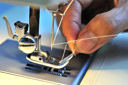 sewing machine: Hand threading needle into sewing needle. For concepts such as fashion and design, work and industrial. Stock Photo