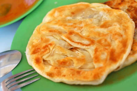 Crispy Indian roti prata cuisine with curry side dish. For diet and nutrition, healthy lifestyle, and Asian cuisine concepts.