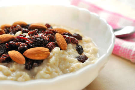 Closeup of nutritious oatmeal topped with rasins and nuts for a healthy breakfast. Also for healthy lifestyle, diet and nutrition, and food and beverage concepts.