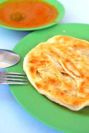 Indian traditional roti prata cuisine with curry side dish. For diet and nutrition, healthy lifestyle, and Asian cuisine concepts.