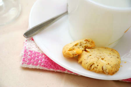 Healthy cookies half eaten with white cup and saucer. A healthy and nutritious afternoon snack. Concepts such as food and beverage, diet and nutrition, and healthy lifestyle. photo