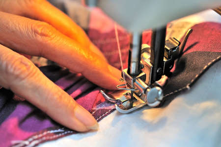 Hand at sewing machine with light on cloth. For concepts such as fashiong and design, work and industrial. photo