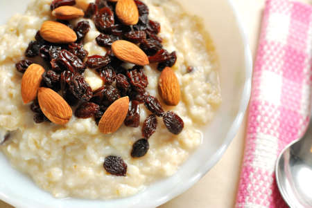 Top view of oatmeal topped with rasins and nuts for a nutritious and healthy breakfast. Also for healthy lifestyle, diet and nutrition, and food and beverage concepts.