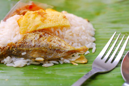 Malay traditional delicacy known as nasi briyani packed in banana leaf. Suitable for concepts such as diet and nutrition, healthy lifestyle, and food and beverage. photo