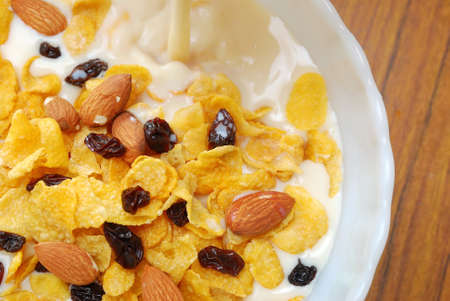 Soya milk pouring into healthy cereal with raisins and nuts for a nutritious and healthy breakfast or meal. Also for healthy eating and lifestyle, diet and nutrition, and food and beverage concepts. photo