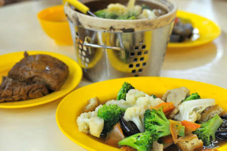 Chinese style vegetarian dishes at a restaurant. Focus on foreground dish. Suitable for concepts such as diet and nutrition, healthy lifestyle, and food and beverage. photo