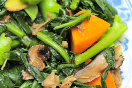 Sumptuous Chinese vegetarian cuisine. Ingredients include green, leafy vegetables, mushrooms, carrots, and slices of ginger.  photo