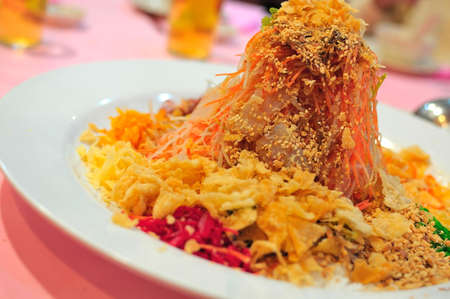 Unique Chinese New Year appetizer dish prepared with colorful vegetables. Widely consumed during the new year for good luck. Stock Photo