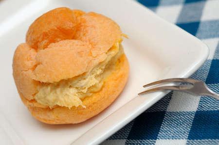 Closeup shot of single freshly baked cream puff on white plate.