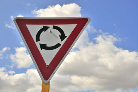 turnabout: Road sign depicting circular turnabout with blue sky background. Stock Photo