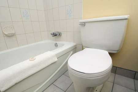 Bright white clean toilet and adjacent bathtub in high class hotel. photo