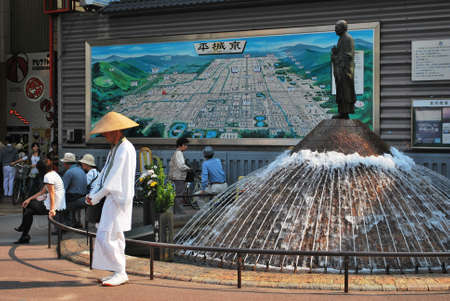 Taken at a clearing outside Nara station on the Kentetsu line in Japan. A monk stands at the fountain asking for alms.