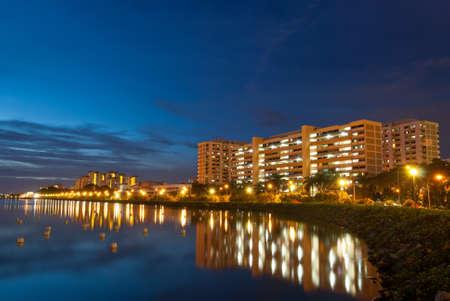 Vista nocturna del barrio residencial tranquilo con reflejo en el lago.