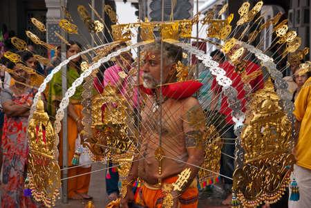 kavadi: SINGAPORE - JANUARY 30: Elder Hindu devotee carrying a golden kavadi at Thaipusam taken on January 30, 2010 in Singapore.