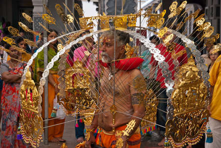 SINGAPORE - JANUARY 30: Elder Hindu devotee carrying a golden kavadi at Thaipusam taken on January 30, 2010 in Singapore.