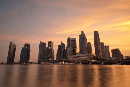SINGAPORE - APRIL 14: Beautiful sunset view of Singapore skyline with reflections in the water bay taken on April 14, 2010 in Singapore. Publikacyjne