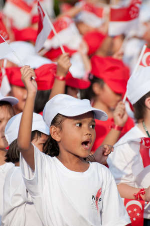 SINGAPORE - AUGUST 9: Little girl dressed in white and waving the national flag proudly on National Day, taken on August 9, 2010 in Singapore. 2010 marks the 45th year of independence. Éditoriale
