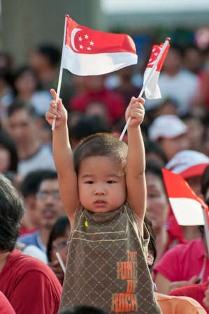 SINGAPORE - AUGUST 9: Cute boy celebrating National Day by holding up flag proudly on National Day, taken on August 9, 2010 in Singapore. 2010 marks the 45th year of independence.