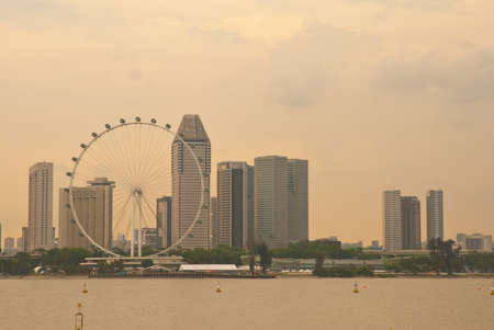 Sunset view of Singapores skyscrapers and majestic Ferris wheel.