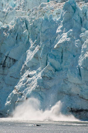 calving: Closeup shot of majestic calving of huge ice glacier into the sea. Stock Photo