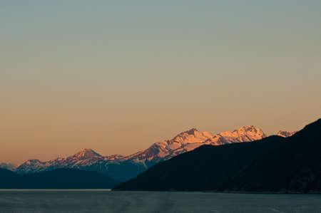 alpen: Majestic snowy mountains lit by alpen glow from golden sunrise.